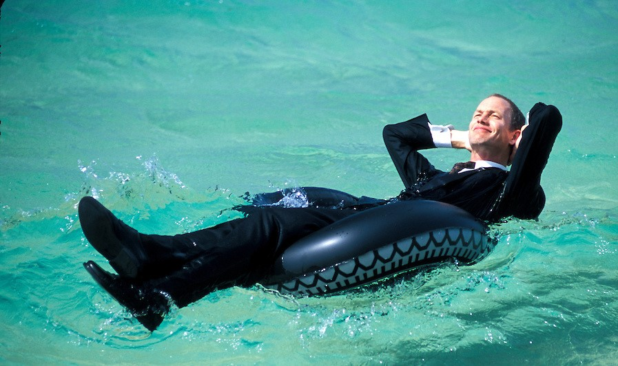 Australia, Queensland, businessman floating on inner tube on calm sea. MR available.
